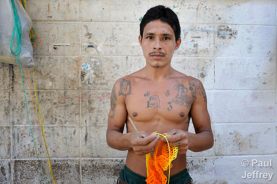 A former gang member makes handbags as a way to earn money in a prison in Sensuntepeque, El Salvador.