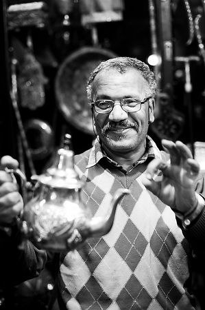 Black and white photo of a Moroccan teapot market vendor in Marrakech souk and market, Morocco, North Africa