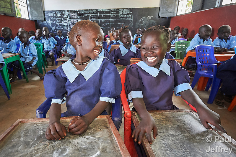 Girls laugh as they hold chalkboard tablets in a primary school in Bunj, South Sudan, sponsored by Jesuit Relief Service. The community is host to more than 130,000 refugees from the Blue Nile region of Sudan, and JRS provides educational and psycho-social services to both refugees and the host community. (Paul Jeffrey)