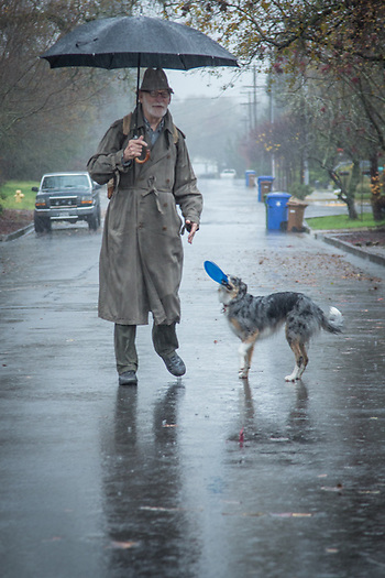"""I bought this coat in New York City 35 years ago...it still comes in handy.""  -Neighbor Jack Ramsey gets harassed by Molly on his way to yoga class on a very rainy day in Calistoga (Clark James Mishler)"