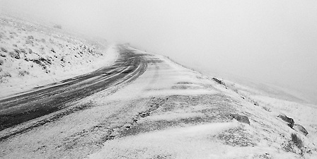 Hurricane force winds scream along the snowy hillside of Steptoe Butte with a road curving upward into zero visibility. (Benjamin Chase / Ben Chase Photography)