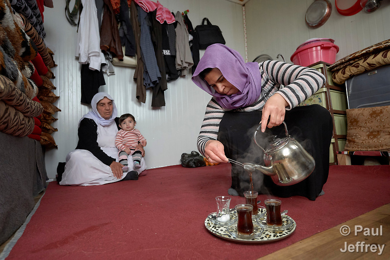 Gole Yaqoub makes tea while her mother-in-law, Adlane Saido, holds Yaqoub's 9-months old child Zylan in a camp for internally displaced Yazidis at Dawodiya in Iraq's Kurdistan region. More than 600 Yazidi families living in the camp escaped from their communities in the Sinjar region during the attempted genocide by the Islamic State group. Although ISIS was militarily defeated in 2017, camp residents say it's still not safe for them to return home, nor do they have sufficient resources to rebuild their homes. The Lutheran World Federation, a member of the ACT Alliance, provides water, sanitation, garbage collection, and psycho-social support for the families in the camp. (Paul Jeffrey)