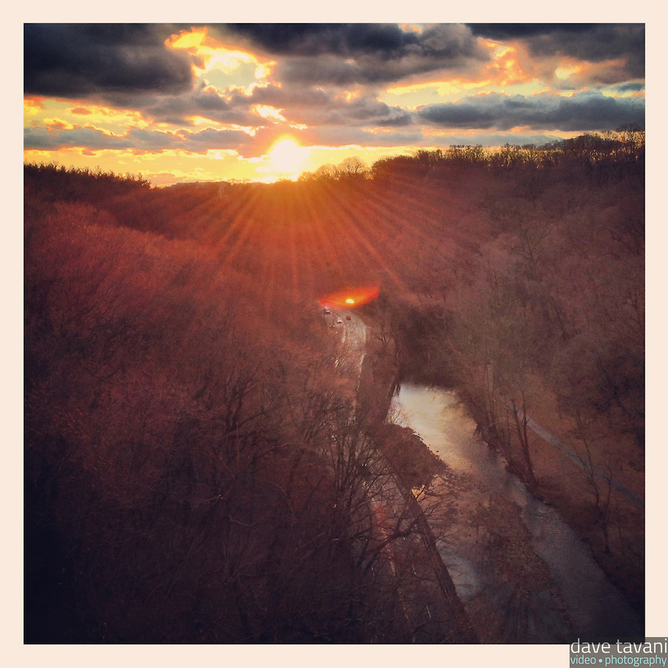 The sun descends toward the horizon over Lincoln Drive and the Wissahickon Creek as see from the Henry Avenue Bridge in Philadelphia December 18, 2012. (Dave Tavani)