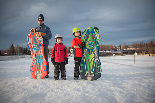 Jon with his sons on the sledding hill at Inlet View Elementary School in Anchorage'e South Addition neighborhood (© Clark James Mishler)