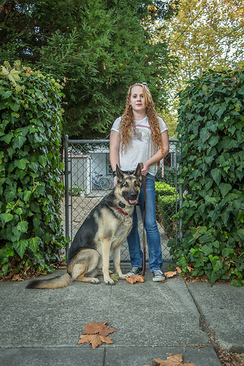 """""""I care for a man born in 1921.  I've avoided telling him that all of his old friends are gone.""""  -Caregiver Cassie Bohan with her three year old German Sheppard, Charley, in front of her home in Calistoga. (Clark James Mishler)"""
