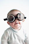 Portrait of 6 month old laughing baby girl wearing welders goggles over eyes (Brad Mitchell/Brad Mitchell Photography)