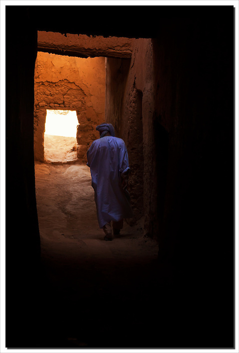 Man dressed in a traditional moroccan gandora walks through a Kasbah. (Rosa Frei)