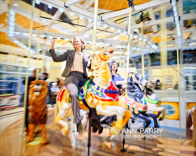 Garden City, New York, USA. March 9, 2019. LAURA CURRAN, the Nassau County Executive, rides Nunley's Carousel carved wood lion during mural unveiling ceremony of Nunley's Carousel horse.(© 2019 Ann Parry/Ann-Parry.com)