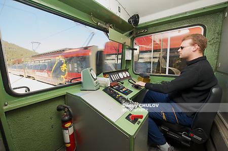CIRCA MONTREUX, SWITZERLAND - DECEMBER 09, 2009: Unidentified man drives Golden pass train locomotive circa Montreux, Switzerland. The Golden Pass line is a major tourist attraction in Switzerland. (Dmitry Chulov)