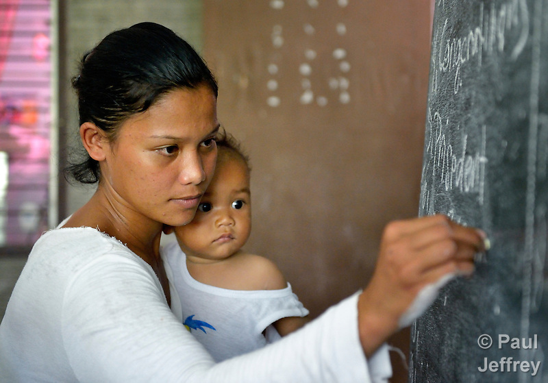 Holding her baby, a woman writes on the blackboard as she participates in an adult literacy class in the village of Magsaysay, in New Bataan in the Compostela Valley on Mindanao Island in the southern Philippines. (Paul Jeffrey)