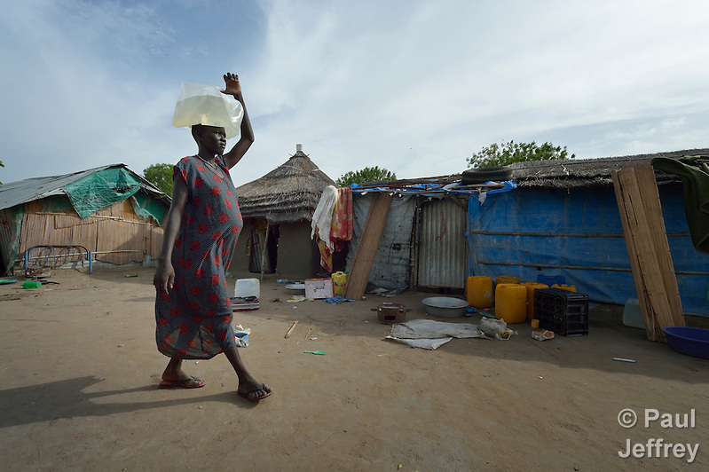 Mou Leu Chol carries water to her home in Bor, a city in South Sudan's Jonglei State that has been the scene of fierce fighting in recent months between the country's military and anti-government rebels. After fighting broke out in mid December 2013, control of the town changed hands four times in a few weeks. ACT Alliance members were among the first humanitarian agencies to enter the city in January 2014, and are providing services to thousands of people who are cautiously returning home to the troubled city. Chol came to Bor in March 2014 to escape continued fighting in nearby Duk County. She and her husband assembled their new home out of the scraps of building materials they found here. The water container she is using is one of several items she received in a household package she received from Dan Church Aid and the Lutheran World Federation, both members of the ACT Alliance. (Paul Jeffrey)