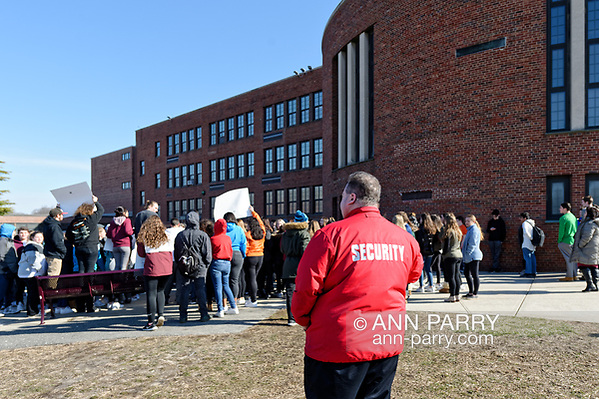 North Bellmore; NY; USA. March 14, 2018. Security Guard in red jacket watches as Mepham High School students, protesting gun violence, walk out of class for 17 minutes; starting 10:00 am. ( © 2018 Ann Parry/Ann-Parry.com)