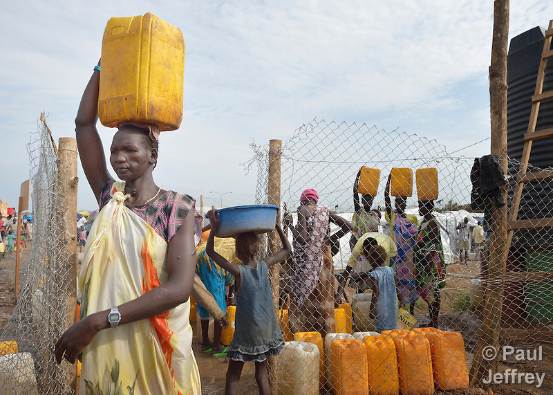 A woman carries water from a communal water point inside a camp for internally displaced families located inside a United Nations base in Juba, South Sudan. The crowded camp holds Nuer families who took refuge there in December 2013 after a political dispute within the country's ruling party quickly fractured the young nation along ethnic and tribal lines. The ACT Alliance is providing a variety of services, including fresh water and sanitation services, to the more than 20,000 people living in the camp. (Paul Jeffrey)