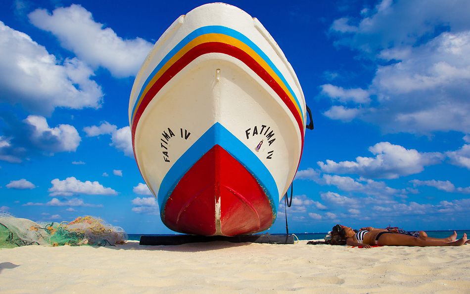 A fishing boat stands beside a pair of sunbathers on the beach in Playa del Carmen, Mexico. (Christopher Gannon)
