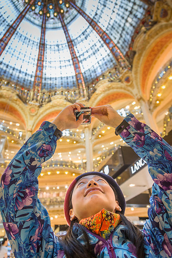 A woman photographs the stained glass dome at Galaries Lafayette in Paris (Clark James Mishler)