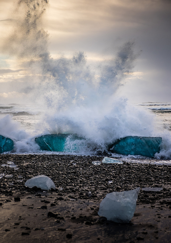 JOKULSARLON, ICELAND - CIRCA MARCH 2015: Waves crashing into an iceberg on the beach near to the Jökulsárlón lagoon in Iceland on the edge of Vatnajökull National Park (Daniel Korzeniewski)