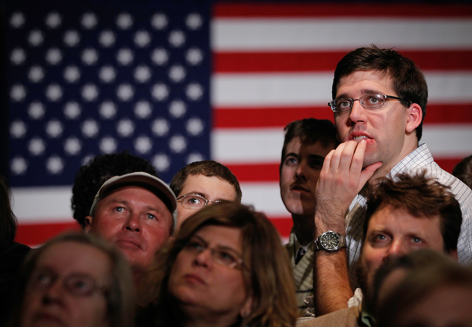 WILLIAM OSBERGHAUS, right, of St. Louis, Mo. watches the close Iowa caucus results with others at Mitt Romney's rally site following the Iowa caucus Tuesday, January 3, 2012 in Des Moines, Iowa. (Christopher Gannon/ZUMA Press)