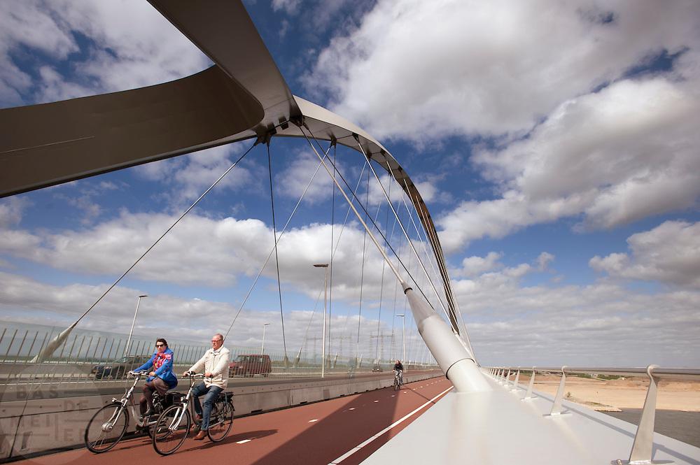 In Nijmegen rijden fietsers op het fietspad aan de Oversteek, de nieuwe verbinding over de Waal aan de noordkant van Nijmegen.