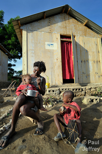 A survivor of Haiti's devastating earthquake, Olginne Pierre sits with her daughter Olginnes and her son Josue in front of a new house in Leogane, south of the Haitian capital of Port-au-Prince. The houses here were built with assistance from the Christian Reformed World Relief Committee, a member of the ACT Alliance. CRWRC is planning more than 1700 houses in the community, and had about half that number completed by the first anniversary of the January 21, 2010 quake. The houses are built on the foundations of the residents' former homes, and are transitional--designed to be improved by residents as they are able. The houses have yet to receive their first coat of paint. CRWRC has also worked with community members on water and sanitation issues in response to the cholera outbreak, and is providing psycho-social support for residents as they rebuild their lives.
