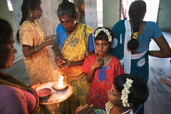 Anjalakshi, age 9, (in red) visits a temple in Pudupettai to mark the Hindu festival of Diwali. She is accompanied by their sisters and maternal grandmother Chitra (yellow sari). The Krishnamurthy sisters spent the Diwali weekend visiting relatives while staying with their father in their home town of Puddupettai.  The five Krishnamurthy sisters from Pudupettai in Tamil Nadu lost their mother to the 2004 Asian Tsunami. Their father declared himself unable to raise his daughters and, like many other tsunami widowers, placed them in the care of a government orphanage. He has since remarried. The sisters, now aged between 6 and 14, have lived with 120 other orphaned children in Cuddalore's Government Home for Tsunami Children since January 2005. Though of course the detail of their lives is unique, the Krishnamurthy sisters share many experiences with other tsunami-orphans in Tamil Nadu and across the tsunami-affected region.  According to staff at the government home, Sivaranjini, age 14, has begun to loose interest in her studies. She fared badly in recent examinations which staff attribute to the poor education she received before the tsunami. The other four sisters are doing well at school. Sivaranjini continues to be a very committed elder sister, undertaking many of a tasks for which a mother would normally be responsible. Sivaranjini washes her sisters' clothes, helps with their studies, offers affection and, when appropriate, administers punishment.  Krishnamurthy, the sisters father, visits the orphange once or twice a month. His sister Kamasala visits more regularly but reserves most of her attention for Sivapriya, age 12. Sivapriya used to live with her paternal aunt before the tsunami. Like other children at the orphange, the five sisters also spend religious festivals and the annual school holidays with their father and extended family. During these periods the Krishnamurthy sisters are treated to gifts and lavished attention from family and friends in (Tom Pietrasik)
