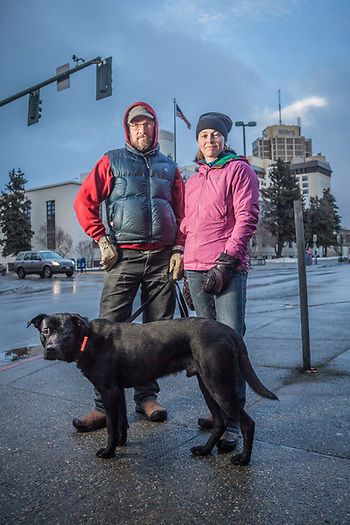 "Kara McMahan and Chad Harder with their dog Budsy on Fourth Avenue in downtown Anchorage.  ""We've lived in Anchorage for two years…we came up from Montana to ski and hunt.  So far, the skiing has been a bust, but Chad did get a Moose this fall.  So, all is not lost.""  ""We are celebrating 16 years of unmarried bliss.""  -Kara McMahan (© Clark James Mishler)"