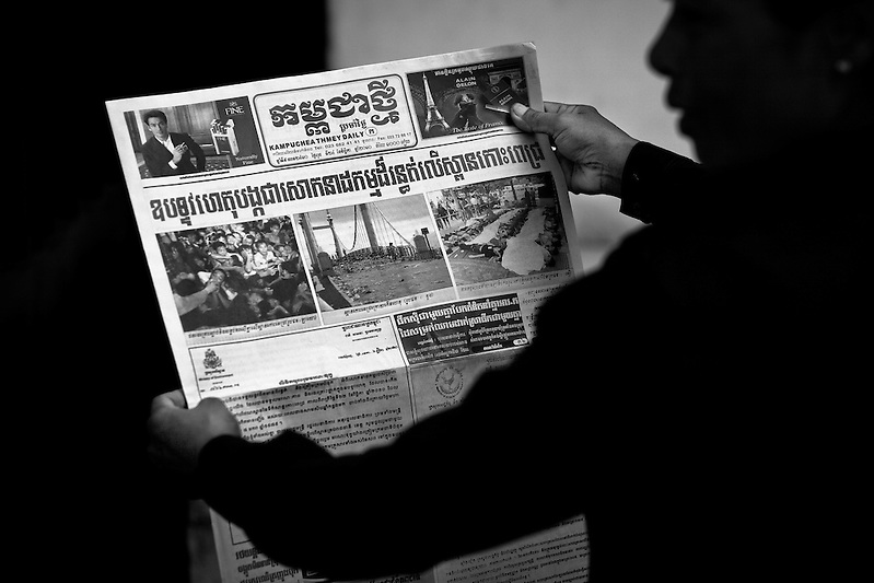A woman reads the newspaper with images and stories of the previous days stampede outside Calmette Hospital in Phnom Penh, Cambodia where many of the victims of the stampede tragedy on November 22nd 2010 were brought. (Quinn Ryan Mattingly)