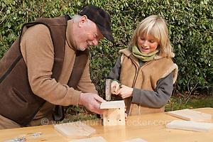 Nistkastenbau, Großvater, Opa und Enkelkind, Kind bauen gemeinsam einen Vogel-Nistkasten für Meisen aus Holz, fertiger Bausatz (Frank Hecker)