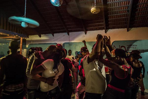 Jóvenes haitianos y dominicanos en una discoteca improvisada en la abandonada Jardín Deportivo. El espacio fue una vez la tienda de tenis del complejo. Crédito Meridith Kohut para The New York Times