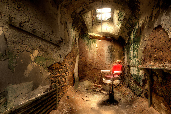 An abandoned old barber chair sits in a decaying jail cell at Eastern State Penitentiary in Philadelphia, PA. (Walter Arnold)