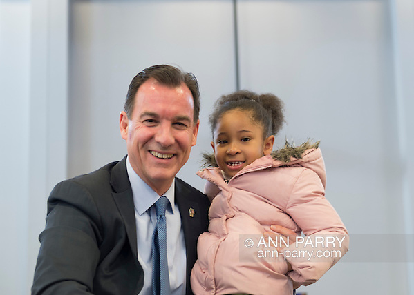 "Westbury, New York, USA. January 15, 2017. Rep. THOMAS SUOZZI (Democrat - 3rd Congressional District) and SANAA SMITH, 5, of Westbury, pose for photo at end ofthe ""Our First Stand"" Rally against Republicans repealing the Affordable Care Act, ACA, taking millions of people off health insurance, making massive cuts to Medicaid, and defunding Planned Parenthood. Sanna attended rally with her mother Naima Smith, who actively advocates for health care. It was one of dozens of Bernie Sanders' rallies nationwide for health care that Sunday. (Ann Parry/Ann Parry, ann-parry.com)"