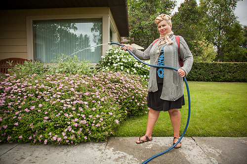 """Gardener Karol Kvale waters a garden in her care in Anchorage's South Addition neighborhood.  """"My grandfather was Norwegian and came to Alaska to work for the Alaska Railroad.  My father was born in the old railroad hospital and my mother was born to one of the original Colony families in the Matnuska Valley.  I have been here all my life."""" (© Clark James Mishler)"""