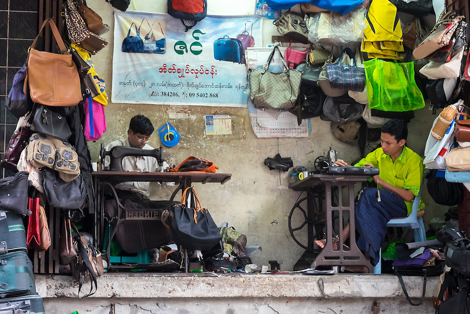 YANGON, MYANMAR - CIRCA DECEMBER 2013: Merchants repairing and selling bags in street market of Yangon (Daniel Korzeniewski)