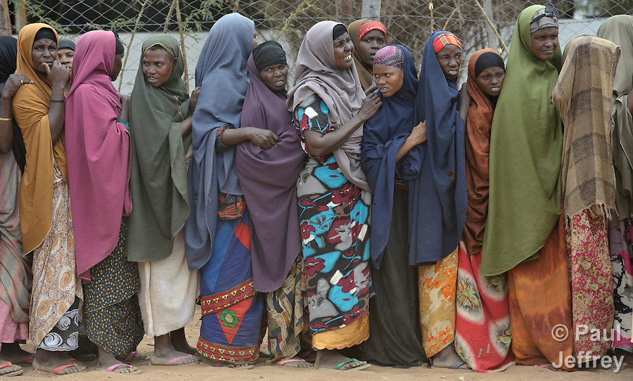 Women stand in line waiting for food and other supplies to be distributed by an Islamic charity in the Hagadera refugee camp, part of the Dadaab refugee complex in northeastern Kenya.