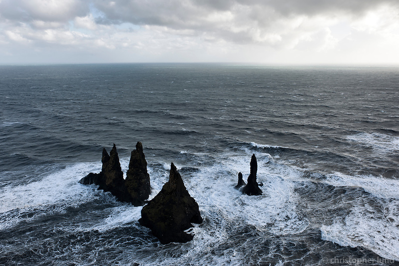 Reynisdrangar, basalt sea stacks situated under the mountain Reynisfjall near the village Vík í Mýrdal, southern Iceland..A Legend says that the stacks originated when two trolls dragged a three-masted ship to land unsuccessfully and when daylight broke they became needles of rock. (Christopher Lund/©2011 Christopher Lund)