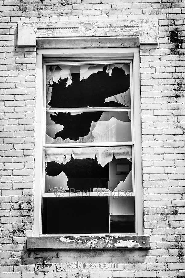 Photo of a broken window at the abandoned Glencoe-Auburn Buildings in Cincinnati Ohio. The Glencoe-Auburn Hotel and Glencoe-Auburn Place Row Houses was built in the late 1800's and is listed on the U.S. National Register of Historic Places. The complex is currently abandoned and in extremely poor condition. (Paul Velgos)