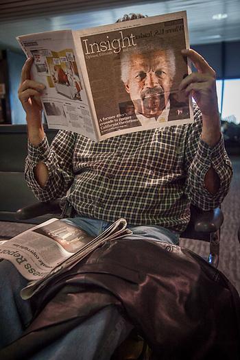 Man reading magazine at Oakland International Airport (© Clark James Mishler)