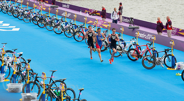 07 AUG 2012 - LONDON, GBR - Alistair Brownlee (GBR) of Great Britain (right) leads the front pack of Jonathan Brownlee, also of Great Britain (left) and Javier Gomez (ESP) of Spain (centre) through transition for the start of the second run lap during the men's London 2012 Olympic Games Triathlon in Hyde Park, London, Great Britain (PHOTO (C) 2012 NIGEL FARROW) (NIGEL FARROW/(C) 2012 NIGEL FARROW)