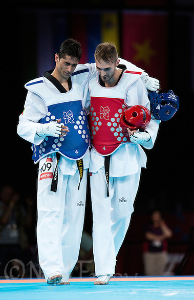 10 AUG 2012 - LONDON, GBR - Mauro Sarmiento (ITA) (right) of Italy helps Nesar Bahawi (AFG) (left) of Afghanistan back to his coach after winning the men's -80kg category bronze medal B contest at the London 2012 Olympic Games Taekwondo at Excel in London, Great Britain (PHOTO (C) 2012 NIGEL FARROW) (NIGEL FARROW/(C) 2012 NIGEL FARROW)