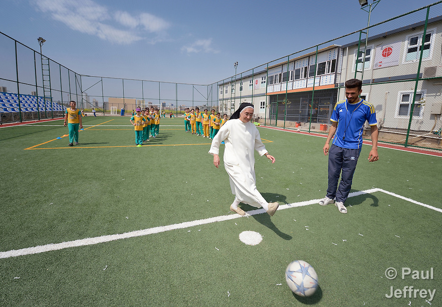 Sister Huda Sheeto kicks a football at the Al Bishara School, which is run by the Dominican Sisters of St. Catherine of Siena in Ankawa, near Erbil, Iraq. Sheeto is the school's principal. The students and the Dominican Sisters themselves were displaced by ISIS in 2014. The nuns have established schools and other ministries among the displaced. (Paul Jeffrey)