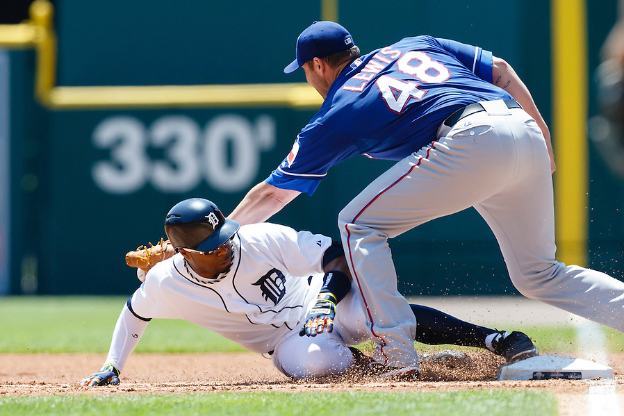 May 25, 2014; Detroit, MI, USA; Detroit Tigers left fielder Rajai Davis (20) slides back to first safe ahead of the throw to Texas Rangers starting pitcher Colby Lewis (48) after he hits a single in the first inning at Comerica Park. Mandatory Credit: Rick Osentoski-USA TODAY Sports (Rick Osentoski/Rick Osentoski-USA TODAY Sports)