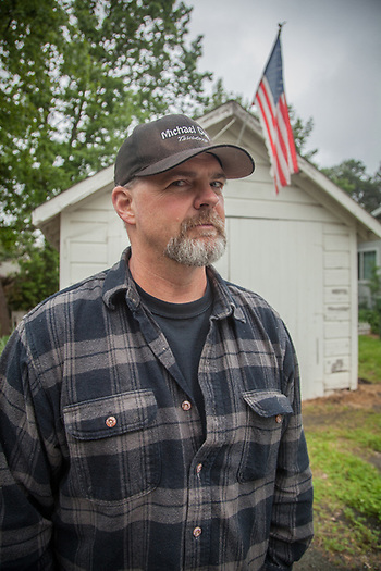"""Winery sales person,Jim Link in front of his garage in Calistoga.  """"I put up this flag from time to time because it reminds me of my dad....he's a Vientnam veteran...won the Silver Star.""""  jimlink1000@yahoo.com (Clark James Mishler)"""