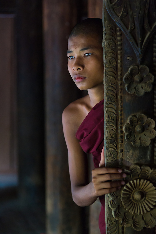 BAGAN, MYANMAR - CIRCA DECEMBER 2013: Young monk peaking through a window in the village of Shwe Kun Cha Hpaya close to Bagan in Myanmar. (Daniel Korzeniewski)