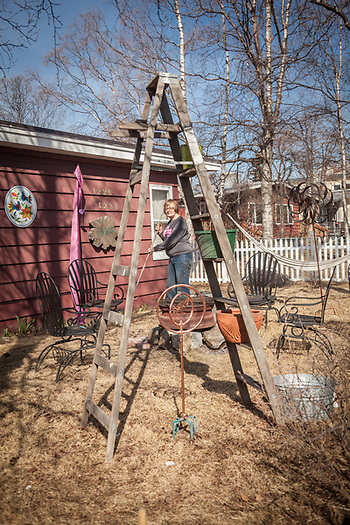 Neighbor Sharron Rooths arranges her eclectic front yard in Anchorage's South Addition neighborhood. (© Clark James Mishler)