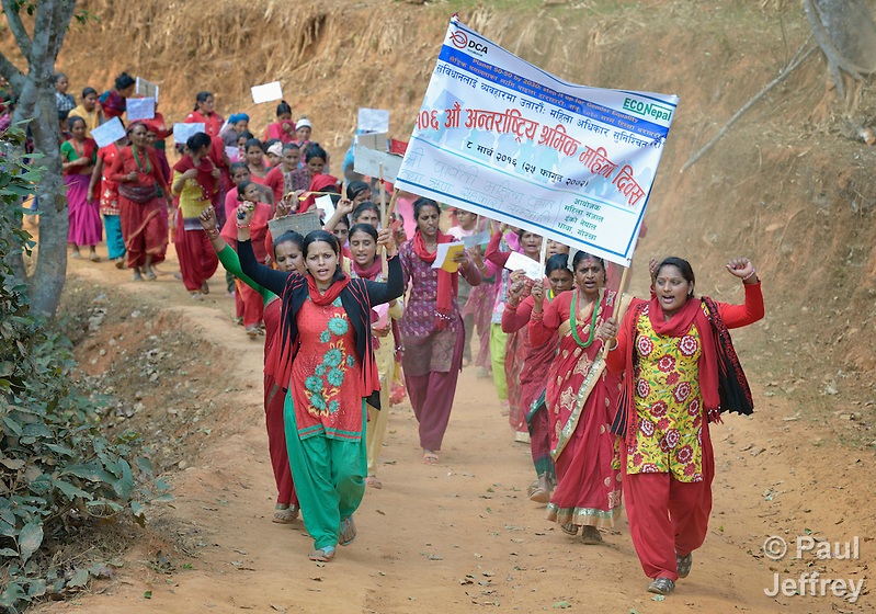 "Women march together in celebration of International Women's Day on March 8, 2016, in Dhawa, a village in the Gorkha District of Nepal. The banner reads, ""106th International Women's Day"" and ""Implement the Constitution and Guarantee Women's Rights."" (Paul Jeffrey)"