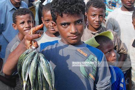 AL HUDAYDAH, YEMEN - SEPTEMBER 17, 2006: Unidentified young fishermen demonstrates catch of the day in Al Hudaydah, Yemen. (Dmitry Chulov)
