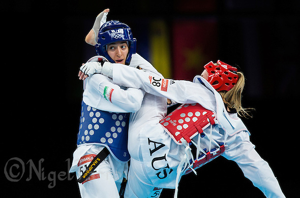 10 AUG 2012 - LONDON, GBR - Sousan Hajipourgoli (IRI) (left) of Iran tries to defend against a kick during her women's -67kg category preliminary round contest against Carmen Marton of Australia at the London 2012 Olympic Games Taekwondo at Excel in London, Great Britain (PHOTO (C) 2012 NIGEL FARROW) (NIGEL FARROW/(C) 2012 NIGEL FARROW)