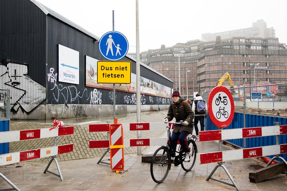 In Utrecht rijdt een fietser langs afzettingen die moeten verhinderen dat er gefietst wordt. De fietser rijdt over een voetpad.