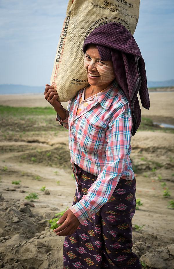 BAGAN, MYANMAR - CIRCA DECEMBER 2013: Young Burmese woman carrying a bag with sand in a village near Bagan (Daniel Korzeniewski)