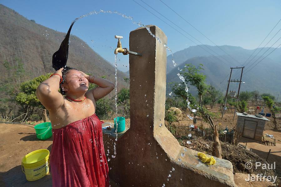 A woman washes her hair in Salang, a village in the Dhading District of Nepal where Dan Church Aid, a member of the ACT Alliance, has provided a variety of support to local villagers in the wake of a devastating 2015 earthquake. The village's water system was destroyed by the quake, forcing women to walk two hours or more to a nearby river to fetch water. Working with a local organization, the Forum for Awareness and Youth Activity, the ACT Alliance rebuilt the village's water system. (Paul Jeffrey)