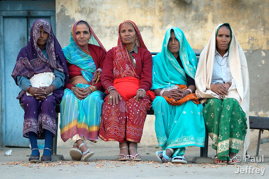 In the northern Indian village of Mursan, traditionally-dressed Hindu women sit in a train station, waiting for a relative to arrive.
